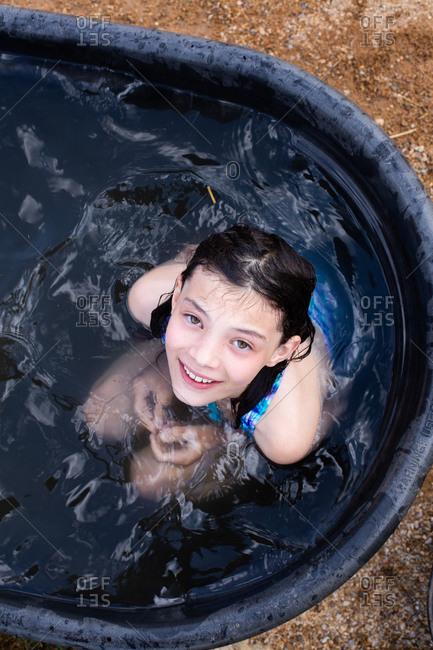 Tween girl looking up while sitting in water trough