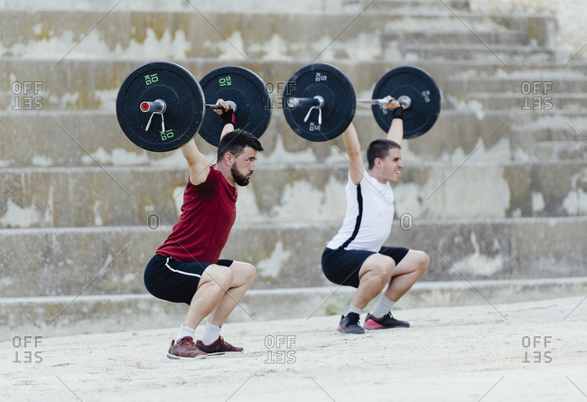 Two weightlifters lifting weights in an urban environment.