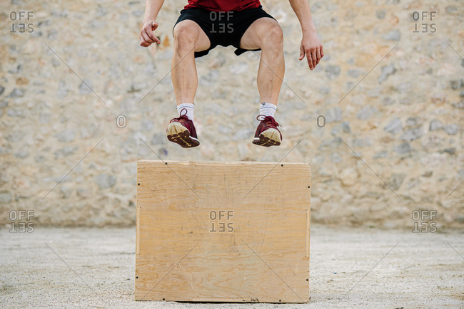 Man practicing crossfit jumping into a plyometric box.