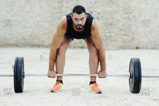 Weightlifter with beard lifting weights in an urban environment.