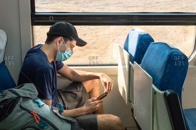 Backpacker with face mask using mobile phone while traveling by train.
