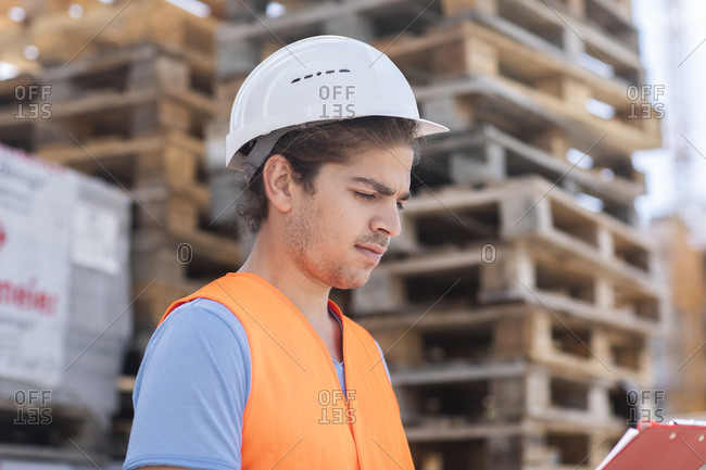 Young store worker with helmet working outside