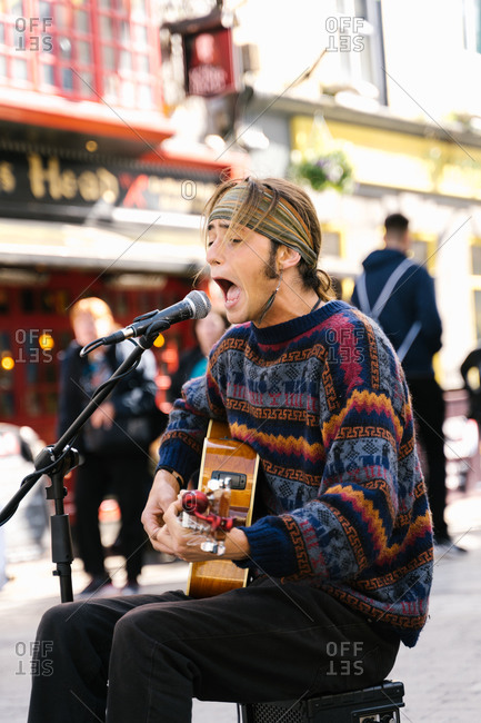 Vertical photo of a young man singing while playing guitar in the street