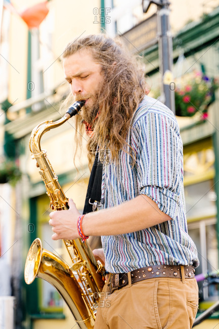 Vertical photo of a young man with long hair playing saxophone in the street