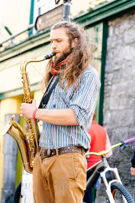 Young man playing saxophone in a crowded street