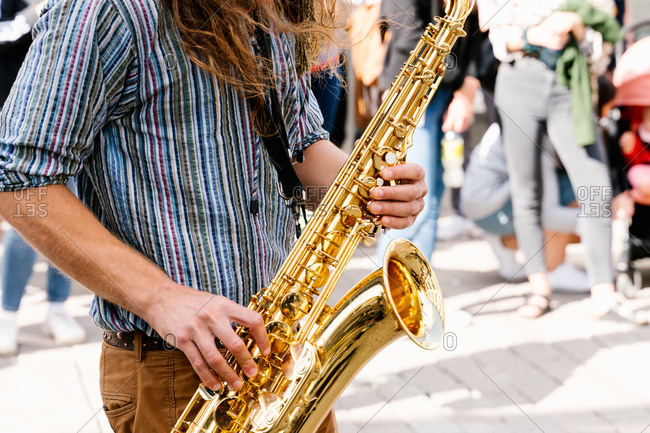 Hands of a young man with long hair playing saxophone in a crowded the street