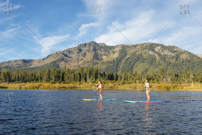 Stand up paddle boarding on lake tahoe next to mount tallac, ca