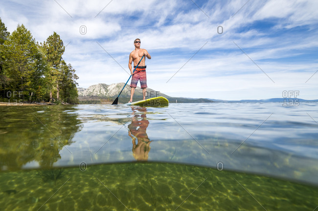 A man stand up paddle boarding on lake tahoe, ca