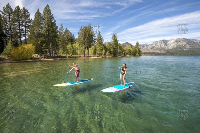 A man and woman stand up paddle boarding on lake tahoe, ca