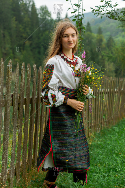 Girl with a bouquet of wildflowers stands on green grass near a wooden fence