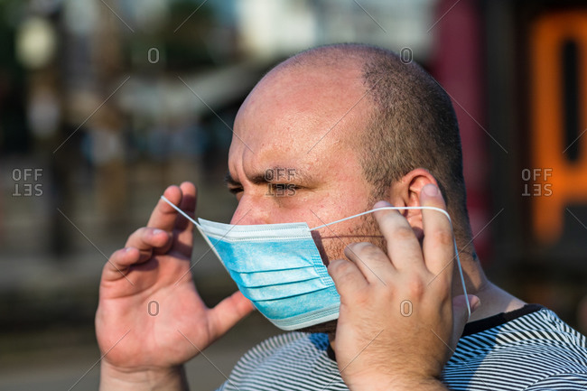 Young man with medical protective face mask illustrates pandemic coronavirus disease on blurred background. sars-cov-2 outbreak in europe. changes and complications caused by epidemic