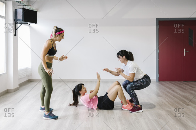 Young and older women in sportswear training with their personal trainer in gym