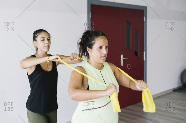 Pregnant woman exercising with rubber bands with her personal trainer