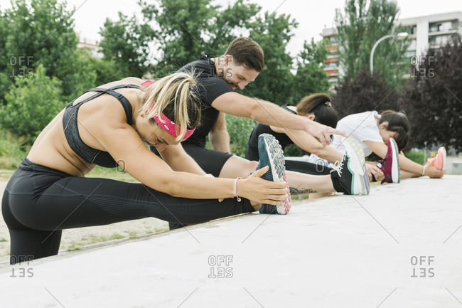 Group of people stretching outdoors after training