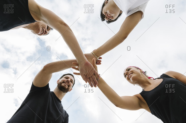 Group of fit people giving a high five for motivation outdoors