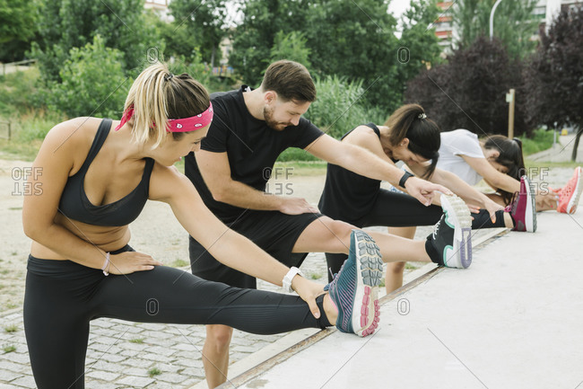 Group of people stretching outdoors with their coach after training