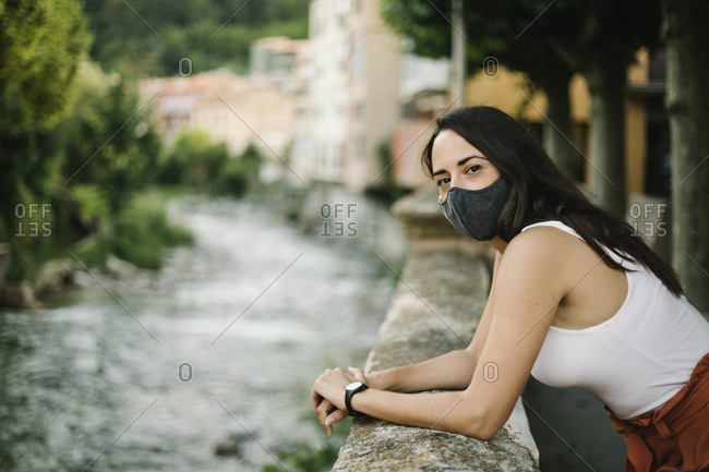 Portrait of woman with crossed arms wearing face mask against a wall