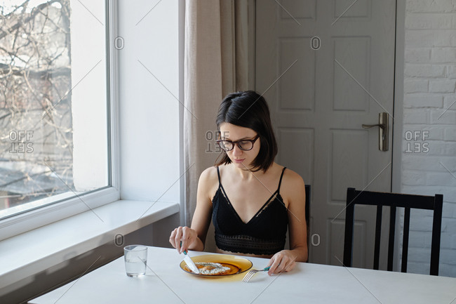 Young woman in lingerie having breakfast by the table