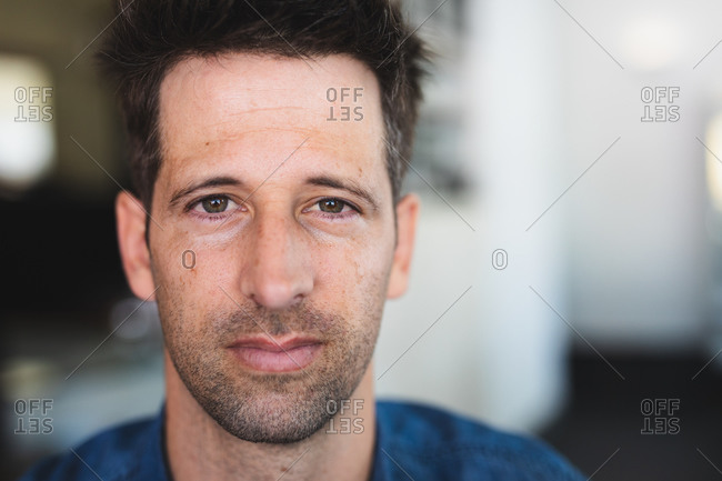 Portrait of a Caucasian man wearing casual clothes, sitting by a table in a coffee shop, looking straight into a camera