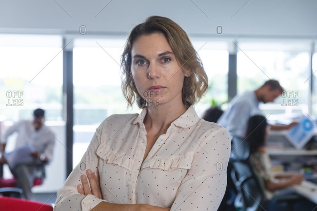 Portrait of confident Caucasian female business creative with arms crossed looking to camera, colleagues working in the background. Creative business professionals working in a busy modern office.