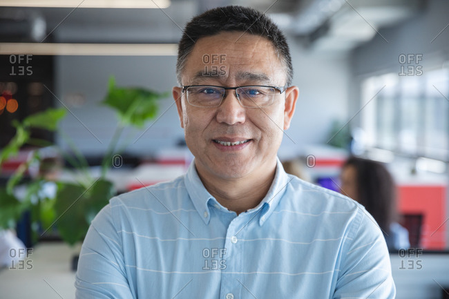 Portrait of smart casually dressed Asian male business creative wearing glasses smiling to camera. Creative business professional working in a modern office.
