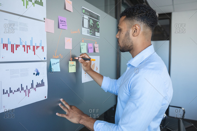Smart casually dressed mixed race businessman writing notes on a magnetic board with charts and information on it. Creative business professional working in a busy modern office.