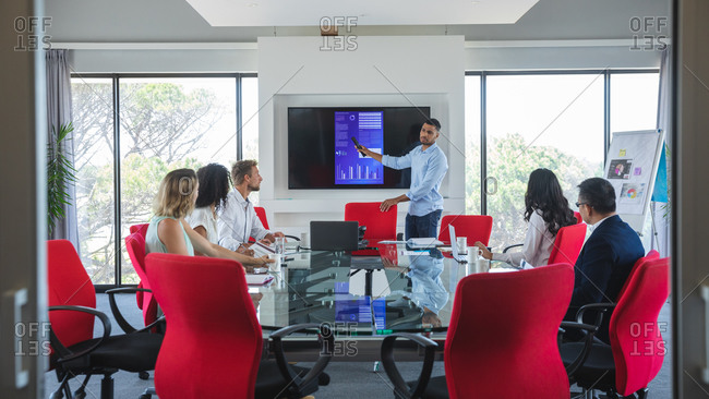 Mixed race businessman standing beside a screen giving a presentation to male and female colleagues sitting in a meeting room. Creative business professionals working in a busy modern office.
