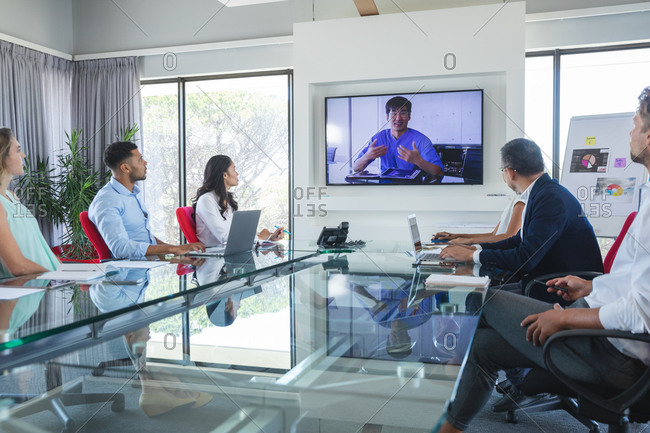 Multi-ethnic group of male and female business colleagues sitting in video conference with an Asian male colleague talking on screen. Creative business professionals working in a busy modern office.