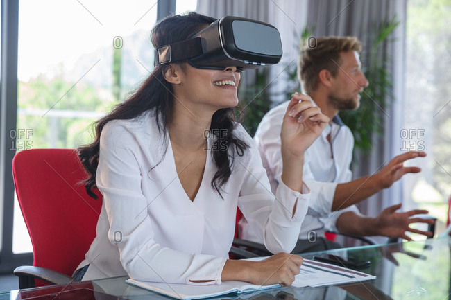 Asian businesswoman sitting at desk using VR headset and smiling, with male colleague discussing in the background. Creative business professionals working in a busy modern office.