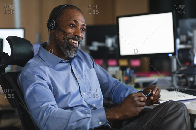 African American businessman working late in the evening in a modern office, sitting at a desk, wearing a phone headset and smiling.
