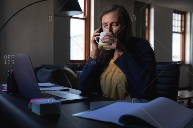 Caucasian woman enjoying time at home, social distancing and self isolation in quarantine lockdown, sitting at table, using a laptop, talking on smartphone and drinking tea.