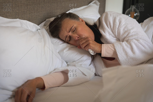 Sick Caucasian woman spending time at home, social distancing and self isolation in quarantine lockdown, lying in bed, coughing.