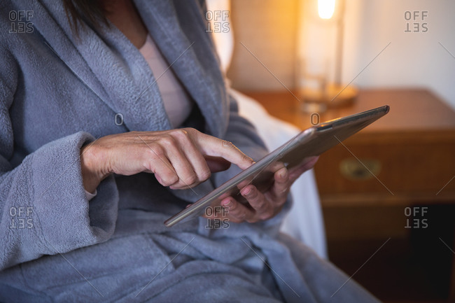 Mid section of Caucasian woman enjoying time at home, social distancing and self isolation in quarantine lockdown, sitting on bed in bedroom, using a digital tablet.