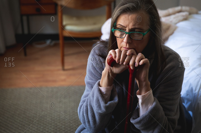 Worried Caucasian woman spending time at home, social distancing and self isolation in quarantine lockdown, sitting in bedroom, holding walking stick.