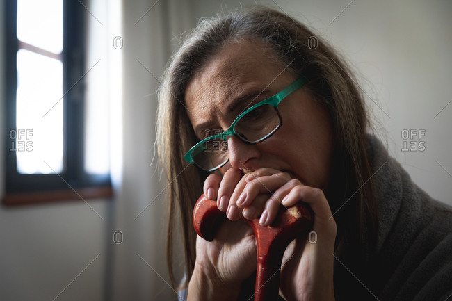 Worried Caucasian woman spending time at home, social distancing and self isolation in quarantine lockdown, wearing glasses, holding and leaning on walking stick.