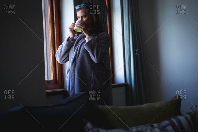 Caucasian woman with long dark hair enjoying time at home, social distancing and self isolation in quarantine lockdown, standing, looking out of window and holding cup of coffee.