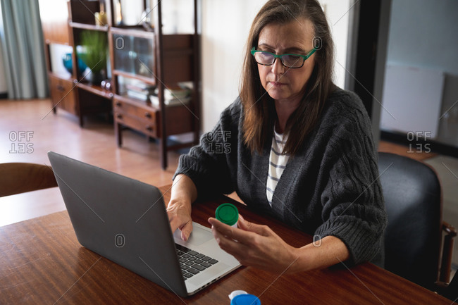 Caucasian woman enjoying time at home, social distancing and self isolation in quarantine lockdown, sitting in living room, using laptop computer, holding medication container.