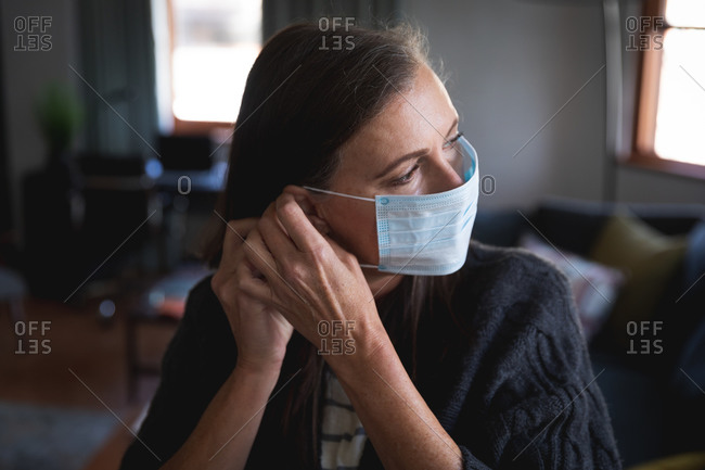 Caucasian woman enjoying time at home, social distancing and self isolation in quarantine lockdown, putting face mask on protecting from Covid 19 coronavirus infection.