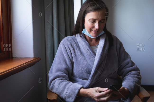 Caucasian woman spending time at home, social distancing and self isolation in quarantine lockdown, with face mask protecting from Covid 19 coronavirus infection, using smartphone.