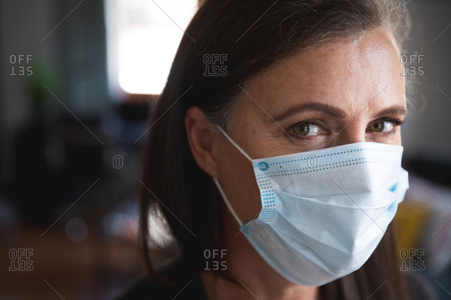 Portrait of Caucasian woman enjoying time at home, social distancing and self isolation in quarantine lockdown, wearing face mask protecting from Covid 19 coronavirus infection, looking at camera.