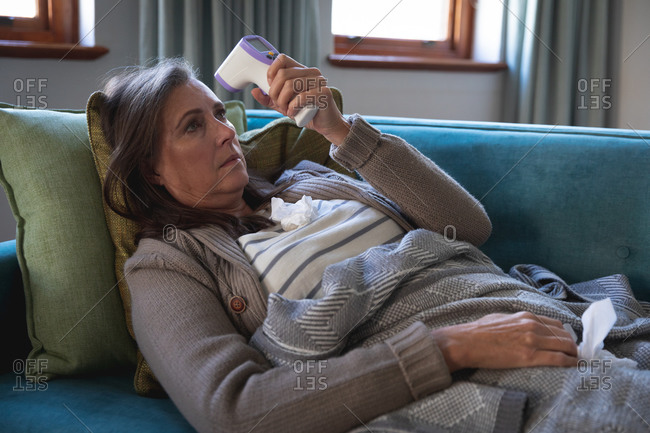 Sick Caucasian woman spending time at home, social distancing and self isolation in quarantine lockdown, lying on sofa covered with blanket, holding thermometer, measuring temperature.