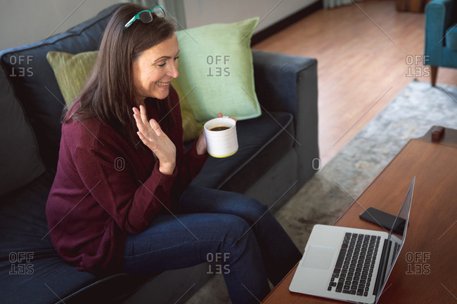 Caucasian woman enjoying time at home, social distancing and self isolation in quarantine lockdown, sitting on sofa in sitting room, using a laptop, waving during video call.