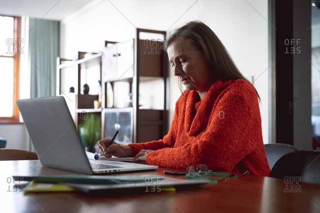Caucasian woman enjoying time at home, social distancing and self isolation in quarantine lockdown, sitting at table, using a laptop, making notes.