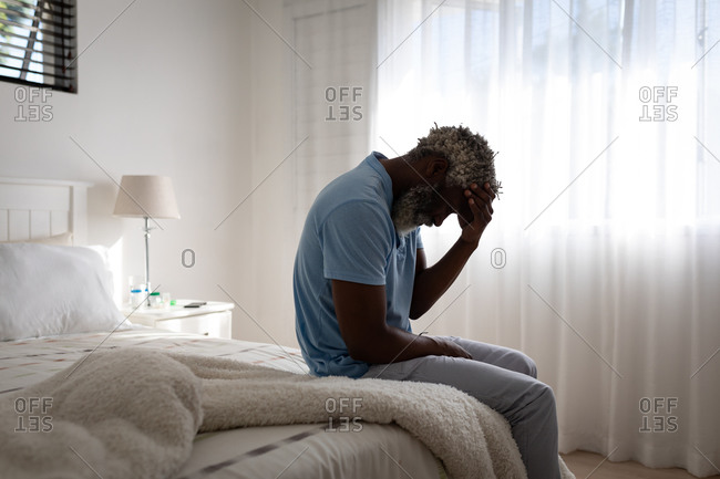 African American senior man sitting on a bed in a bedroom, holding his forehead in his hand, social distancing and self isolation in quarantine lockdown