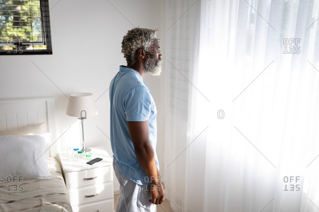 African American senior man standing in a bedroom, looking through a window, social distancing and self isolation in quarantine lockdown