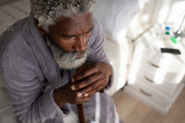 African American senior man sitting on a bed in a bedroom, resting his head on a cane, social distancing and self isolation in quarantine lockdown