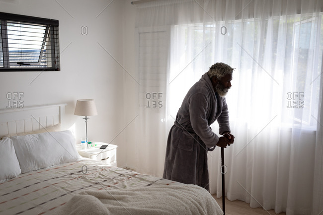 African American senior man walking with a cane in a bedroom, social distancing and self isolation in quarantine lockdown