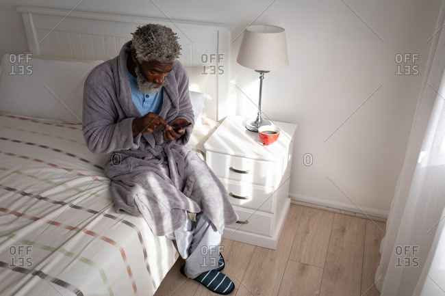 African American senior man sitting on a bed in a bedroom, using a smartphone, social distancing and self isolation in quarantine lockdown