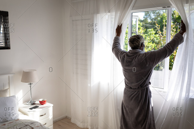African American senior man standing in a bedroom, drawing curtains of the windows, social distancing and self isolation in quarantine lockdown