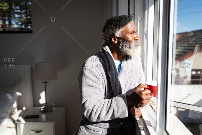 African American senior man standing in a bedroom, holding a cup of coffee, looking through a window, social distancing and self isolation in quarantine lockdown
